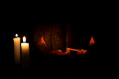 暗い背景にハロウィーンのカボチャとキャンドル。ハロウィンイブバナーテンプレート。不気味な顔を刻んだカボチャ。