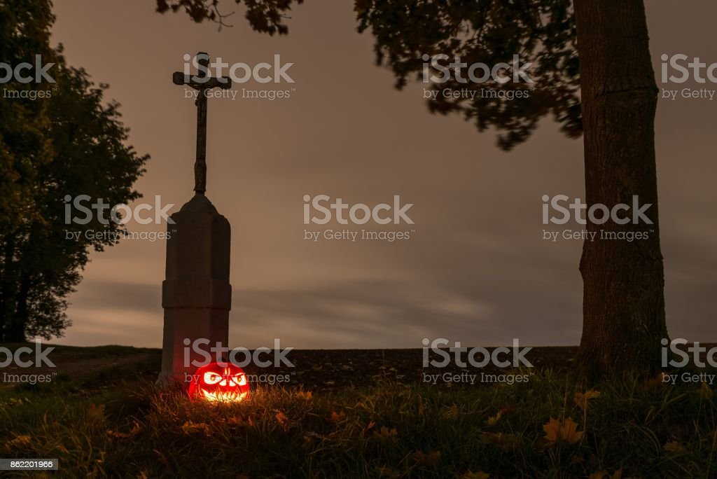 Halloween pumpkin beside a way cross with leaves and tree trunk stock photo