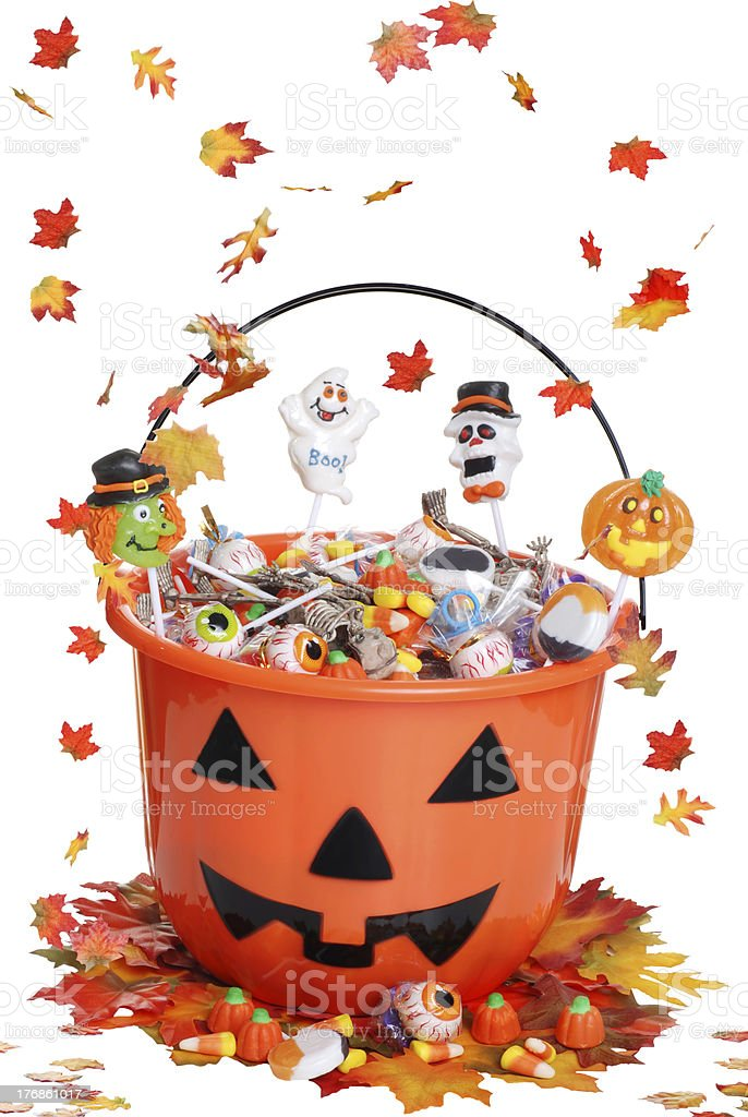 halloween pumpkin bucket with candy and falling  leaves stock photo
