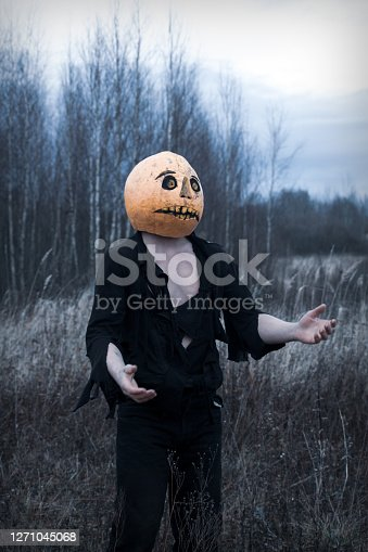 Lost in the woods a guy in a pumpkin with a lantern with a candle wanders in search of a means of getting rid of the autumn depression