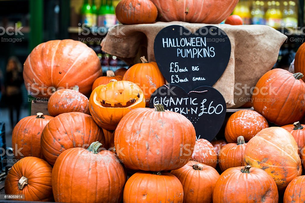 Halloween Pumpkin Display at Borough Market, London, UK A display of large, small and carved pumpkins for Halloween in Borough Market, a famous food market in London, UK. There is a board showing the prices for the pumpkins, £3 for a small one, £5 for a big one, and £60 for a 'gigantic' pumpkin. Horizontal colour image with copy space. Agricultural Fair Stock Photo