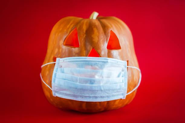 calabaza de halloween en una máscara médica protectora sobre un fondo rojo - halloween covid fotografías e imágenes de stock
