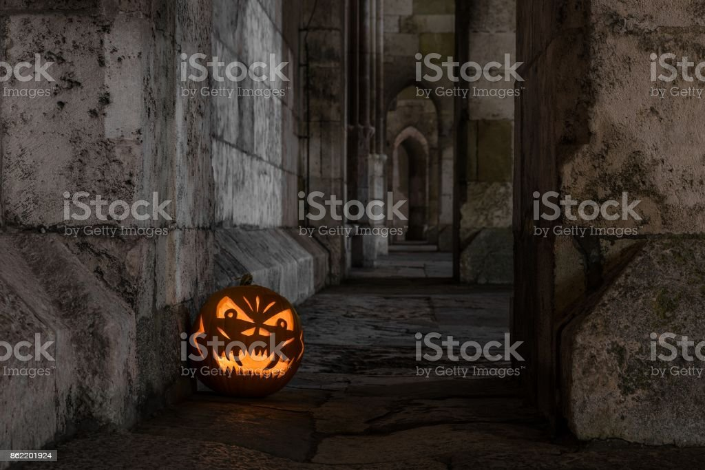 Halloween pumpkin in front of ancient stone wall of a church, Germany stock photo