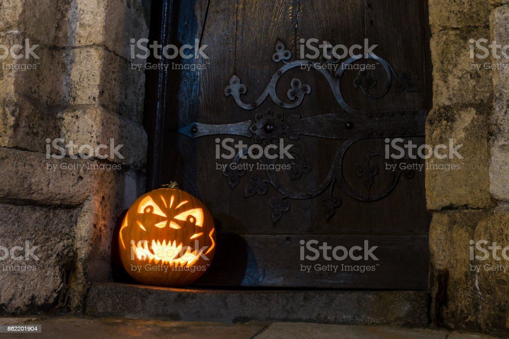 Halloween pumpkin in front of ancient wooden door and stone wall of a church, Germany stock photo