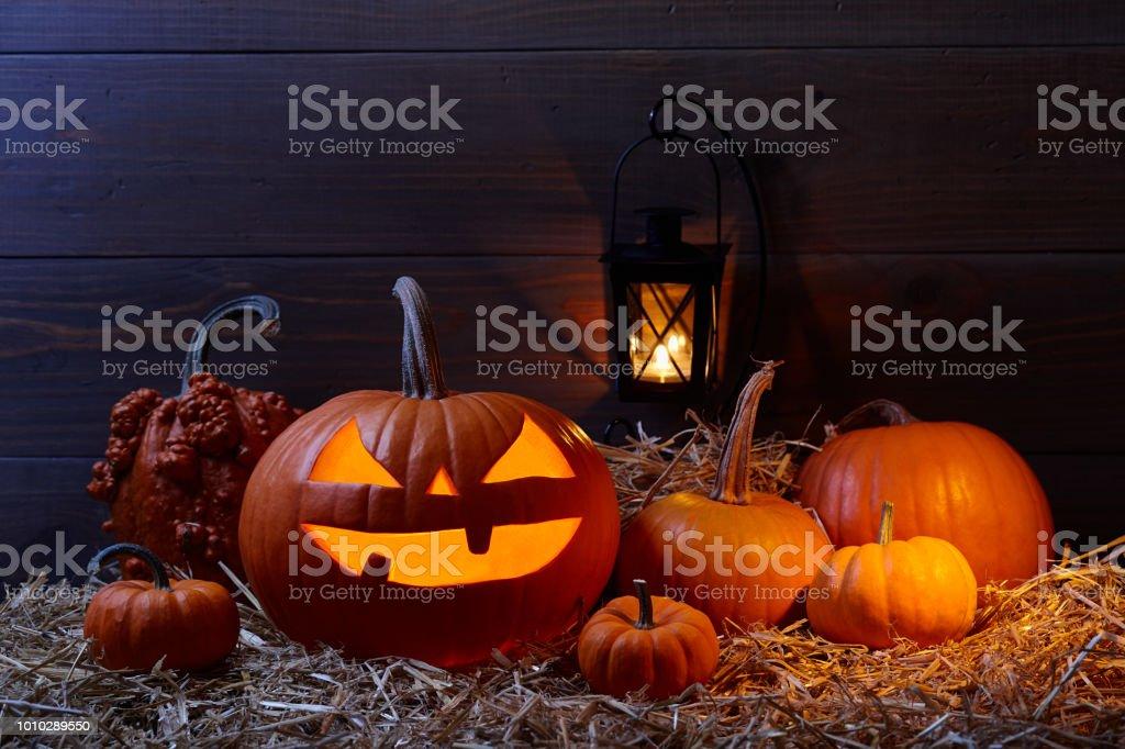 Halloween pumpkin jack lantern in dark barn, holiday concept stock photo