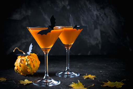 Halloween pumpkin orange cocktails. Festive drink. Halloween party. Funny Pumpkin with holiday decorations