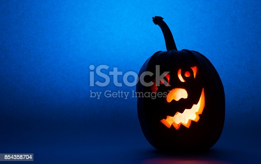 istock Halloween pumpkin, silhouette of funny face on blue background 854358704
