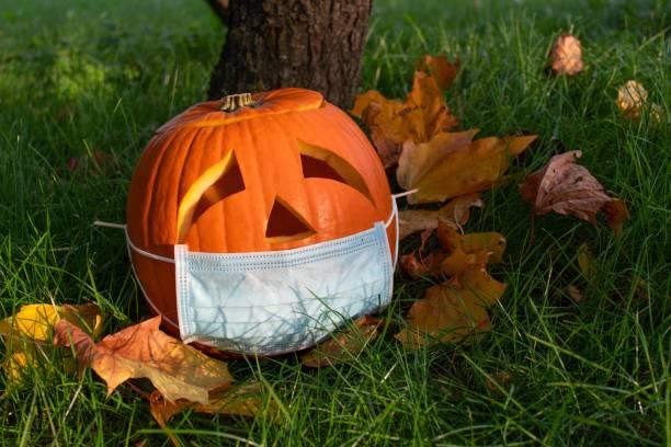 calabaza de halloween con ojos tristes usando máscara - halloween covid fotografías e imágenes de stock
