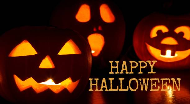 Halloween - pumpkins and candles with a warm and cold glow, against the background with text happy halloween stock photo