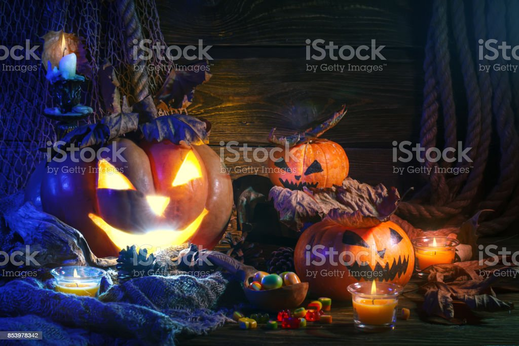 Halloween pumpkins and candy on wooden table at night stock photo