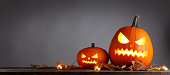 Halloween pumpkins head jack o lantern and dry maple leaves on wooden background