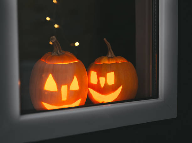 Halloween pumpkins at windows with bokeh. Happy Halloween day stock photo