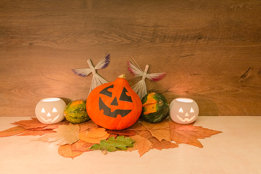istock Halloween pumpkins, burning squash shape lanterns, straw angels, and dry autumn leaves on wooden background 1168010775