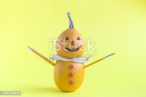 598064660istockphoto Halloween pumpkins in form of snowman on yellow background minimal creative concept. 1051324576
