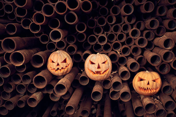 Halloween Pumpkins on a stack of rusty pipes stock photo