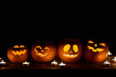 Halloween pumpkins in a row with candles over black background with copy space for text above, front view