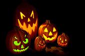 Pumpkins lit up on black.