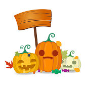 Halloween pumpkins with wooden board, sweets and autumn leaves