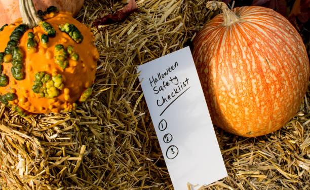 Halloween safety checklist with pumpkins on haystack stock photo