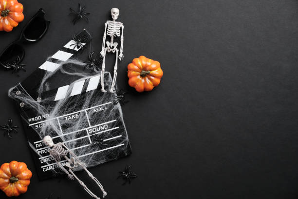 Halloween scary movie concept. Flat lay composition with clapper board, skeleton, spider web, pumpkins on black desk. Halloween background.