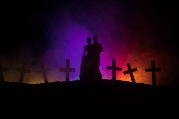 Halloween. Scary zombie bride on a night cemetery holds a pumpkin lantern. – zdjęcie