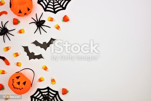1057069236 istock photo Halloween side border of candy and decor, flat lay over white 1032890262
