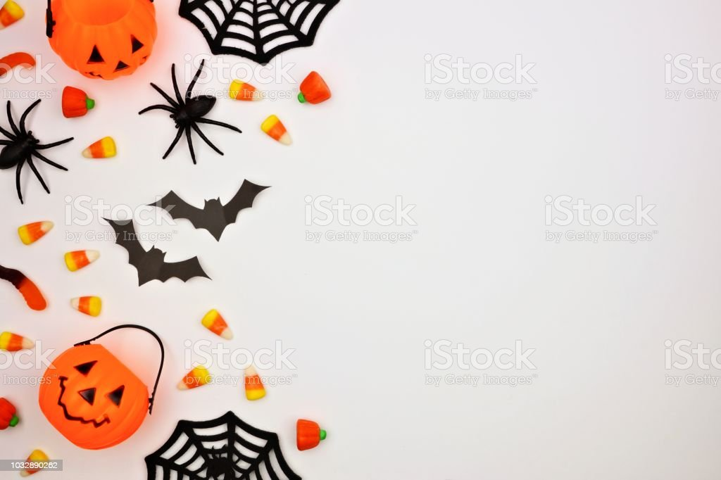 Halloween side border of candy and decor, flat lay over white stock photo