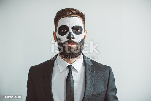 Young man celebrating Halloween with make up costume of skeleton in suit