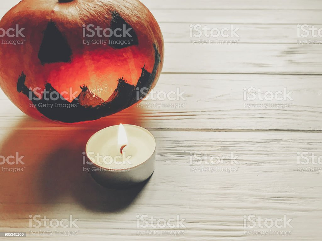 halloween. spooky jack lantern pumpkin with with candle light on wooden background. holiday celebration. seasonal greetings. happy halloween concept, space for text royalty-free stock photo
