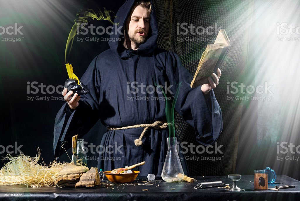 Halloween. The medieval alchemist conducts holding a skull with candle stock photo