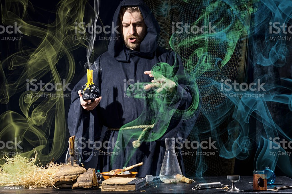 Halloween. The medieval alchemist  in his laboratory in the smoke stock photo