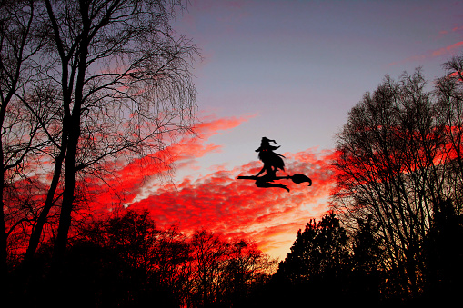 istock Halloween. The witch flying on the broom with the burning red eyes against the background of the night sky. 852230520