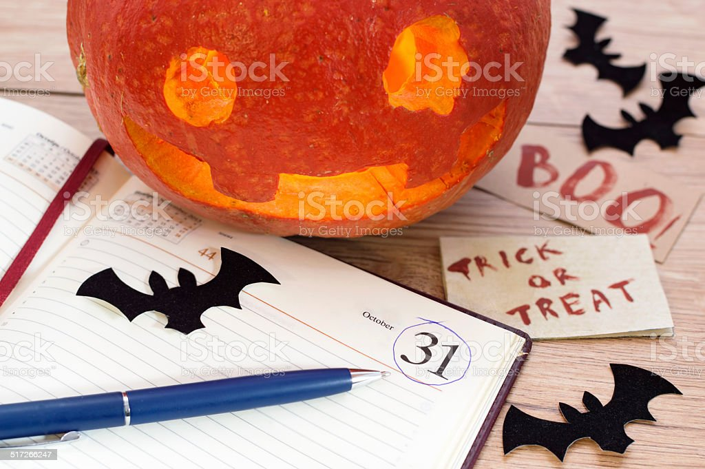 Halloween theme 3 Pumpkin head with open diary, black bats and blue pen 30-34 Years Stock Photo