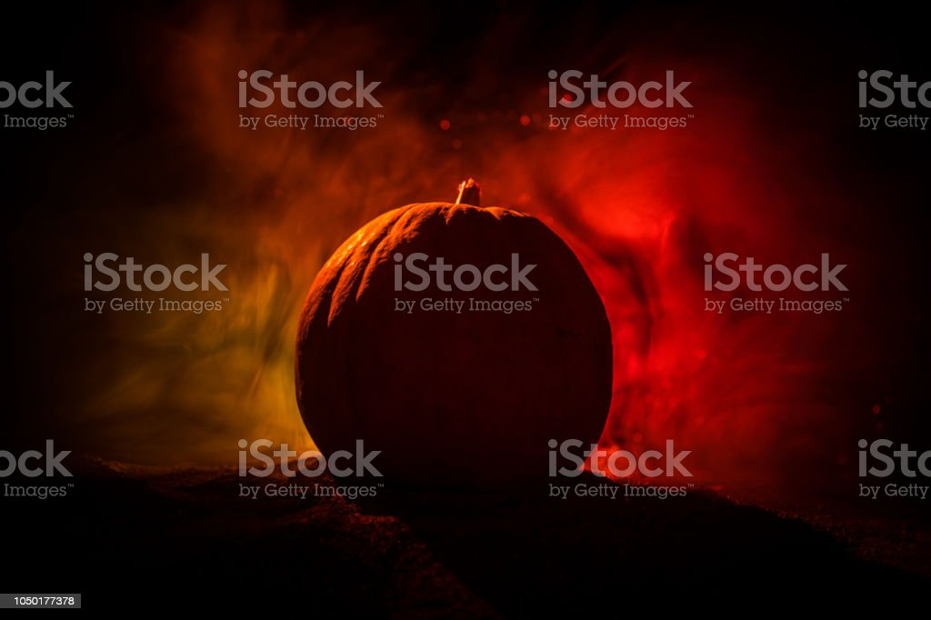 Halloween theme with pumpkin against smoky dark background. Empty...