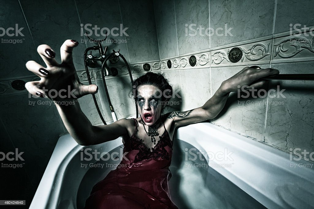 Halloween theme.Scary girl in bath. stock photo