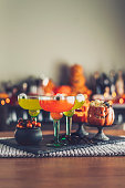 Halloween time. Vibrant colored drinks with cauldron of candy