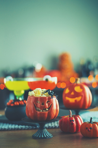 Halloween time. Vibrant colored drinks with cauldron of popcorn