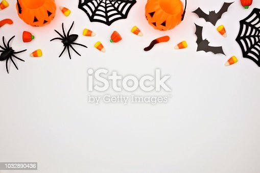 1057069236 istock photo Halloween top border of candy and decor, flat lay over white 1032890436