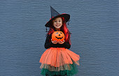 istock Halloween trick or treat. Portrait smiling girl in witch hat against a blue wall . Copy space for text 1279592624