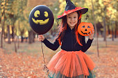 istock Halloween trick or treat. Portrait smiling girl in witch hat with black balloon . Funny kid in carnival costumes outdoors. 1279288762