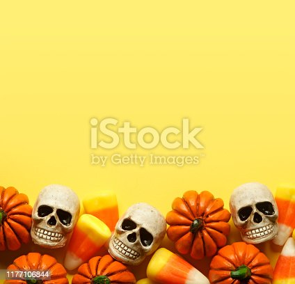 A group of toy pumpkins, skulls, and candy corn sit at the base of a bright yellow background that provides ample room for copy and text.