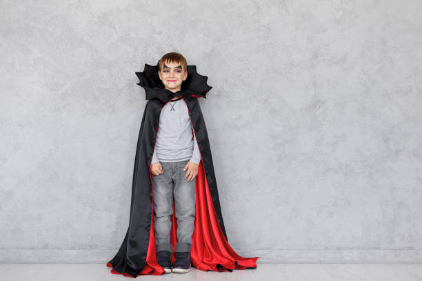 Halloween vampire boy Smiling boy with vampire makeup and black, red cloak with bat like collar on a gray textured background. Halloween mood, copy space available. Cute kid wearing halloween costume. fang stock pictures, royalty-free photos & images