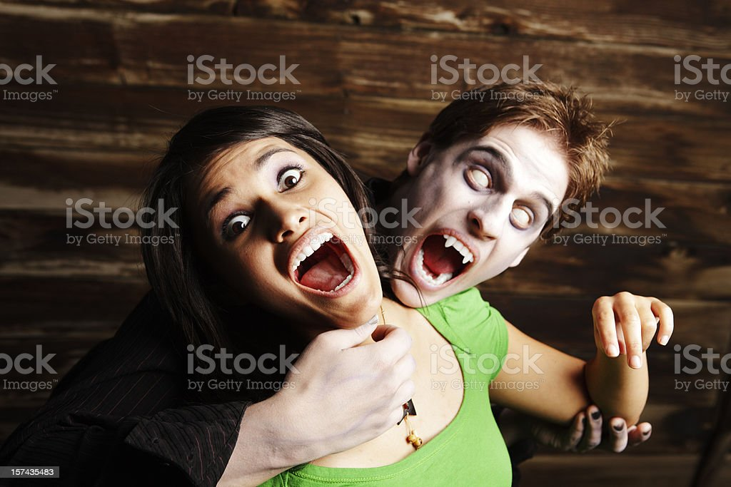 Halloween: vampire with weird eyes ready to bite screaming victim royalty-free stock photo
