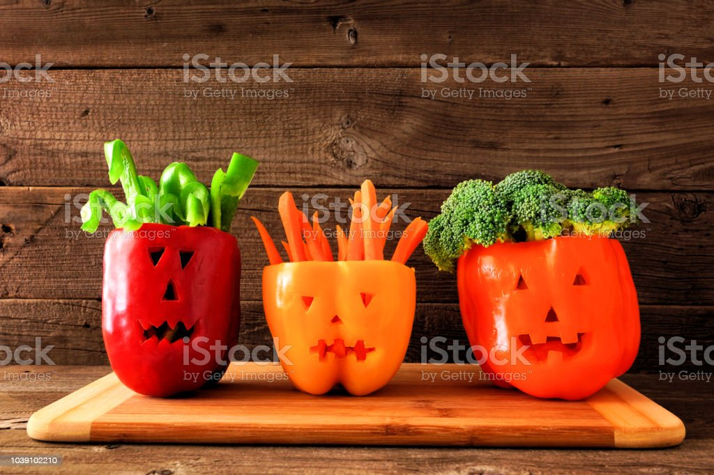 Halloween vegetables and dip in Jack o Lantern peppers on a wood background stock photo