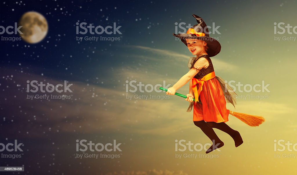 Halloween. Witch child flying on broomstick at sunset night sky. stock photo