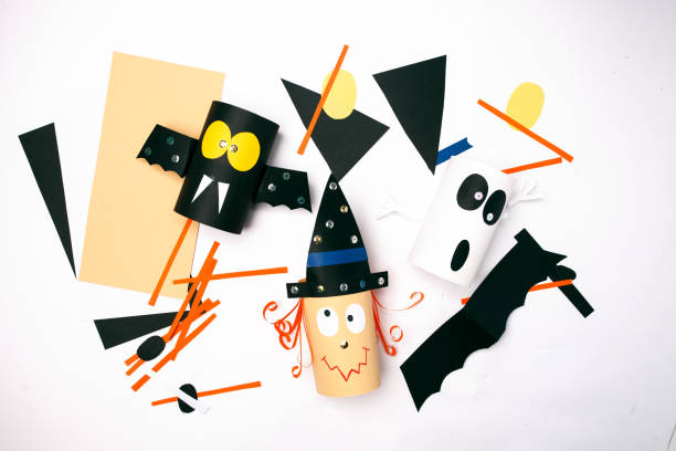 halloween-hexe, gespenst, fledermaus aus papier auf weißem hintergrund. kreatives basteln für kinder. home deko-idee für party. work in progress - minimalistischer kindergarten stock-fotos und bilder