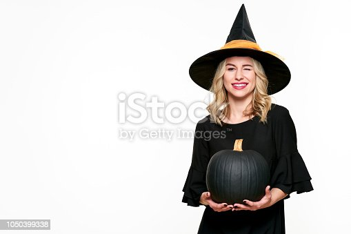 512061362 istock photo Halloween Witch holding large black pumpkin winking. Beautiful young woman in witches hat and costume holding pumpkin over white background. 1050399338