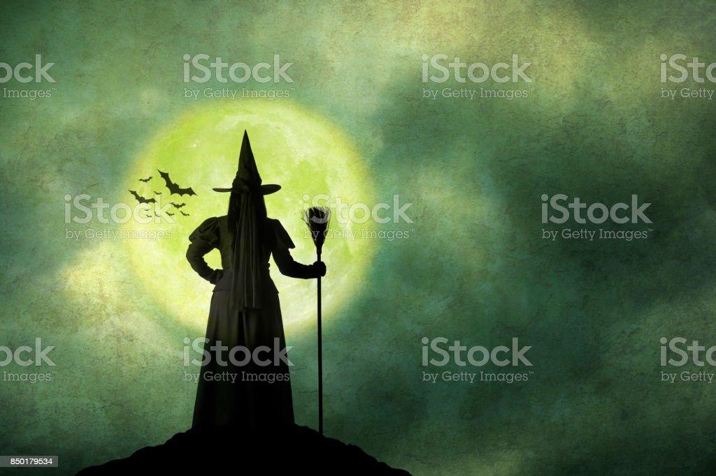 Bruja de Halloween tiene su escoba de pie delante de luna llena - foto de stock