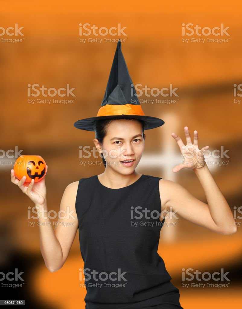 Halloween Witch with a magic Pumpkin on orange background. royalty-free stock photo