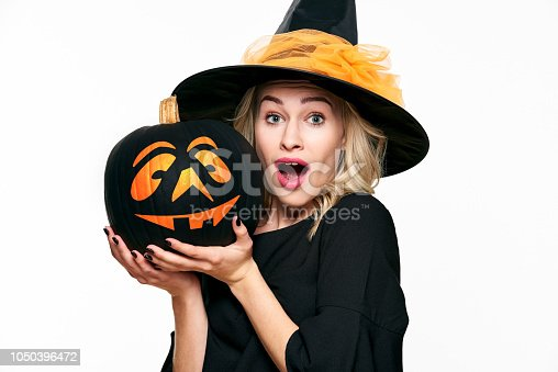 512061362 istock photo Halloween Witch with shocked expression holding a Jack o Lantern. Beautiful young woman in witches hat and costume holding pumpkin over white background. 1050396472